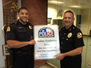 Flower Mound Police Chief Andy Kancel and another officer hold one of the new signs for the online transaction exchange areas during the Monday night town council meeting. (Photo by Dawn Cobb)