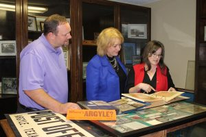 Argyle Town Manager Paul Frederiksen, left, Mayor Peggy Krueger and Kay Teer, councilmember, look through some of the historical books created by Teer's mother, former mayor Yvonne Jenkins, inside what will become a new satellite museum at Argyle Town Hall. (Photo by Dawn Cobb)