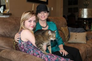 Taryn, left, and her mother, Julia Leahy, sit with the family cat in the family living room at their Lantana home. (Photo by Dawn Cobb)