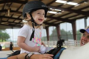 Two-year-old Mia Steedley smiles as she sits astride a horse slowly walking around arena, guided by therapists and volunteers with Victory Therapy Center (Photo by Dawn Cobb).