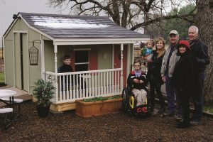 Standing next to newly-finished Bartonville playhouse include (from left) Liam Robinson, Conley Robinson, Trish Robinson holding Bella Robinson in addition to volunteer Jerry Morgan, Executive Director Sandra Monclova and Art Locke, board member, from Habitat for Humanity of Denton County.  (Photo by Bill Castleman)
