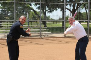"""Flower Mound Police Chief Andy Kancel and FM Fire Chief Eric Greaser take warm-up swings for the """"Backing the Badge"""" softball game."""