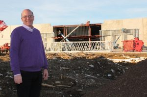 Flower Mound Town Council member Bryan Webb stands near the construction of the Lakeside Moviehouse & Eatery, which is expected to open this spring at Lakeside DFW.