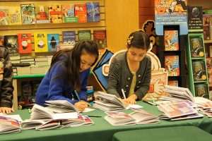 Young Authors Cynthia Guima and Fatimas Avelar of Rivera Elementary sign copies of their published work that will be on display in their campus' library. Fourth and fifth graders from across the district were honored for their exceptional writing and artistic skills at an annual event sponsored by  Denton ISD Adopt-A-School.