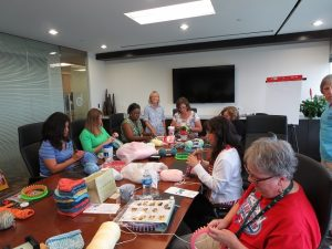 Employees from Berkley Specialty Underwriting Managers learn how to loom knit, creating more than 300 handmade hats for Love Thy Baby.